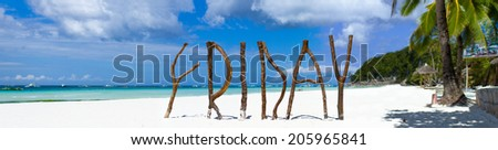 Panorama of postcard perfect exotic beach with white sand and turquoise clear water on tropical island with wooden letters making Friday word - stock photo