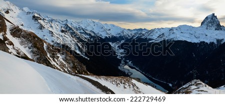 Panorama of Pyrenees mountains is photographed from Artouste ski resort. There are a lake (Lac de Fabreges), a river and  the peak du Midi d'Ossau at the right. - stock photo