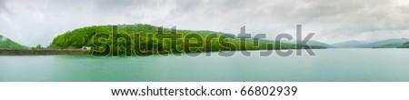 Panorama of reservoir coast and rainy sky - stock photo