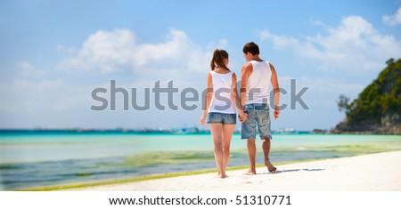Panorama of romantic couple on white sand beach - stock photo