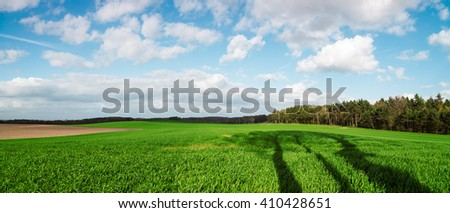 Panorama of sky clouds and grass on meadow. - stock photo