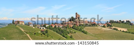Panorama of small typical italian town with medieval castle, hill, vineyards and mountains on the background in Piedmont, Northern Italy. - stock photo