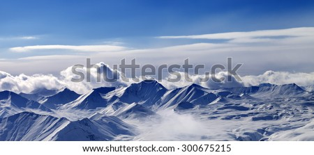 Panorama of snow plateau and sunlight sky in evening. Caucasus Mountains, Georgia. View from ski resort Gudauri. - stock photo