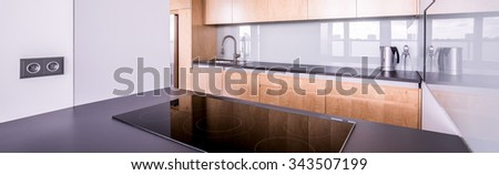 Panorama of spacious kitchen with modern and functional cooking area - stock photo