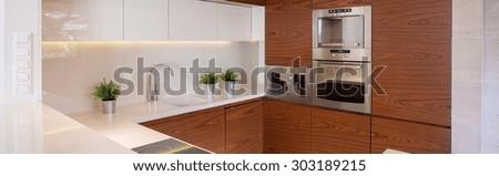 Panorama of stylish kitchen with decorative wood imitation tiles - stock photo