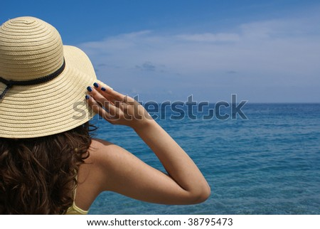 Panorama of summer sea and sky with a beautiful woman standing on the beach - stock photo