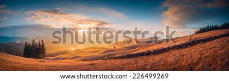 Panorama of sunset in a Carpathian mountain valley with wonderful gold light on a hills - stock photo