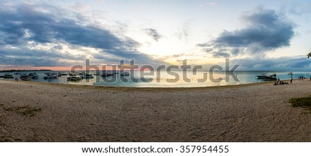 Panorama of sunset or sunrise on beach with water reflection and a small sun on the horizon. - stock photo