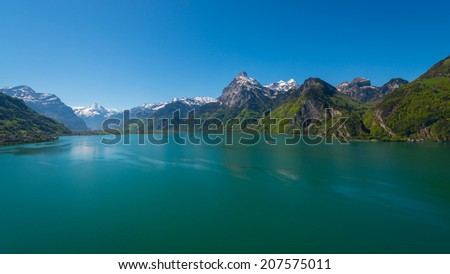Panorama of Swiss Alps, peaks covered with snow.  Lake Uri in central Switzerland. Gorgeous summer day and clean bright blue sky - stock photo