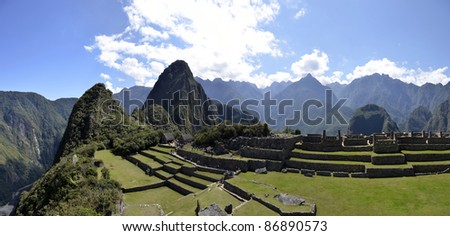 Panorama of Terraces Machu Pichu with Huayna Picchu in Peru, rainforest jungle and mountains with blue sky in the background - stock photo