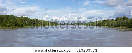Panorama of the Amazon river and the rain forest with a cloudy blue sky. Amazon States, Brazil - stock photo