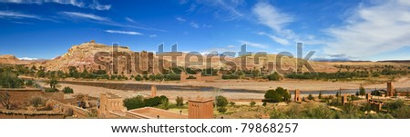 Panorama of the ancient moroccan kasbah Ait Benhaddou, near Ouarzazate - Unesco world heritage. Snow covered Atlas mountains can be seen in the background. - stock photo