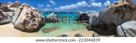 Panorama of The Baths beach area major tourist attraction at Virgin Gorda, British Virgin Islands with turquoise water and huge granite boulders, perfect for banners - stock photo