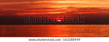Panorama of the beautiful sunset at sea - stock photo