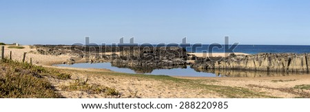 Panorama of  the calm Indian Ocean waves breaking on grey weathered  basalt rocks at  Ocean beach Bunbury Western Australia on a fine sunny  morning in mid   summer are cool and refreshing. - stock photo