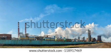 Panorama of the chemical factory throwing out polluting smoke from pipes in the blue sky - stock photo