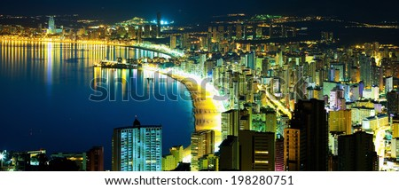 Panorama of the city by the sea in a summer sunset and the night lights of the city reflected in water (Spain, Benidorm) - stock photo