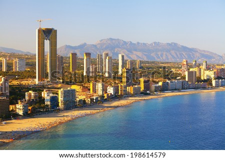 Panorama of the coast with people sunbathing and swimming people on background city hotels and houses (View of the Benidorm before sunset, Spain) - stock photo