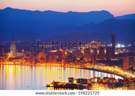 Panorama of the coastal city at sunset with lights reflected in sea (Spain, Benidorm) - stock photo