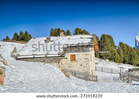 panorama of the Dolomites with wood cottage,  snow-capped peaks and green conifers - stock photo