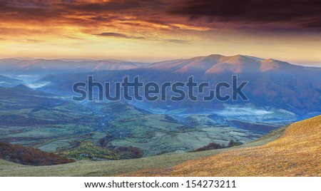 Panorama of the dramatic autumn sunset in the mountain - stock photo