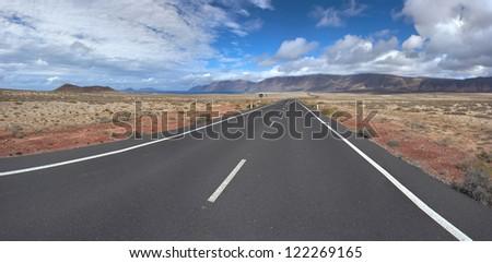 Panorama of the empty road through sandy and volcanic desert. Canary Islands, Lanzarote. View on the Caleta de Famara and Famara beach. - stock photo