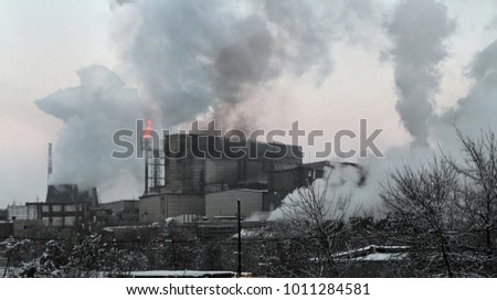 Panorama of the industrial complex with a large torch of burning gas from the pipe and huge smoke. Pollution of the environment by factories with obsolete technologies and absent filters and treatment