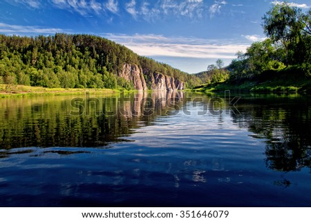 Panorama of the lake among hills with blue sky - stock photo
