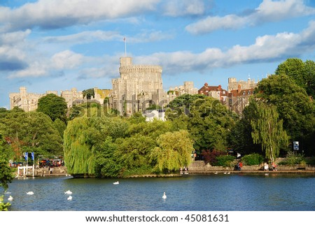 Panorama of the mighty Windsor castle, the home of the Queen, with the river Thames and boat trips docks in the foreground - stock photo