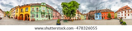 Panorama of the Sighisoara Citadel Square or Fortress Square, Romania. Colourful medieval houses with dramatic skies. Panoramic montage from 14 HDR images