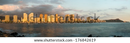 Panorama of the skyline of Honolulu and Waikiki from Ala Moana park as the sun sets and illuminates the facades of the hotels and apartments - stock photo