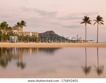 Panorama of the skyline of Waikiki at dawn taken with a long exposure to blur out movement in the water and provide a reflection of Diamond Head in Hawaii - stock photo