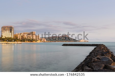 Panorama of the skyline of Waikiki at dusk taken with a long exposure to blur out movement in the water. Breakwater leads the eye towards the volcano of Diamond Head in Hawaii - stock photo
