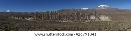 Panorama of the snow covered peaks of the Guallatiri volcano (6063 m) and Parinacota volcano (6342m) towering above the Altiplano and valley of the River Lauca in Lauca National Park, northern Chile. - stock photo