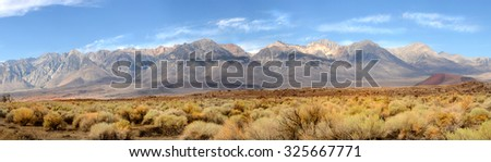 Panorama of the southern tip of the Sierra Nevada Mountains located in Central California under a clear blue sky with wispy white clouds. - stock photo