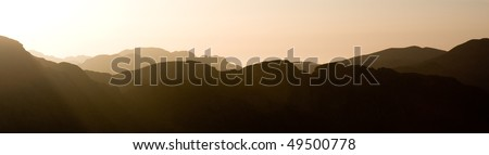 Panorama of the sun setting over misty mountains - stock photo