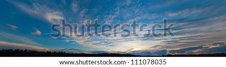 panorama of the sunset sky with clouds over the wood - stock photo