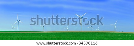 Panorama of the wind turbnes on a summer field - stock photo