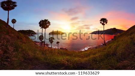 Panorama of tropical coast with beach,  palm trees and island in calm sea at twilight. Nai Harn's beach area of Phuket. Thailand - stock photo
