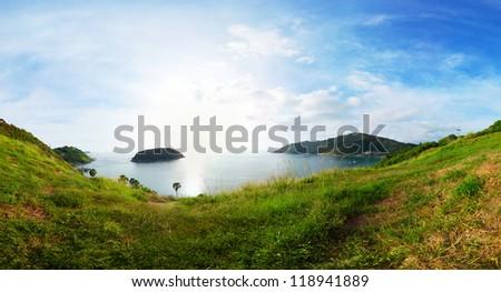 Panorama of tropical coast with  island in calm blue sea. Nai Harn beach area of Phuket. Thailand - stock photo