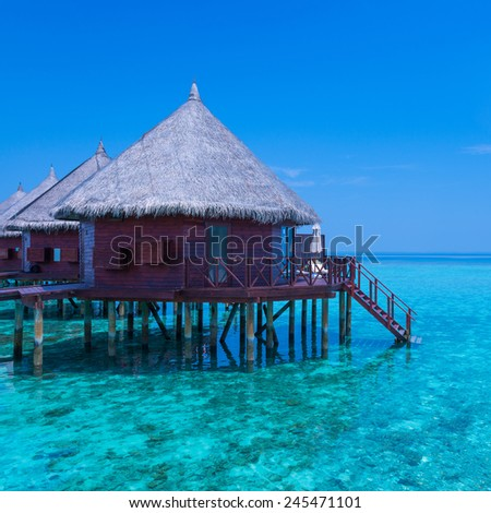 Panorama of tropical island resort with over-water bungalows. Blue sky with a few clouds. Turquoise water of lagoon. - stock photo