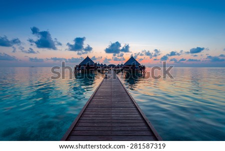 Panorama of tropical island.  Turquoise water lagoons, coral reefs visible. Sunrise sky and clouds painted in pink. Tourist Resort Deluxe. Maldives - stock photo