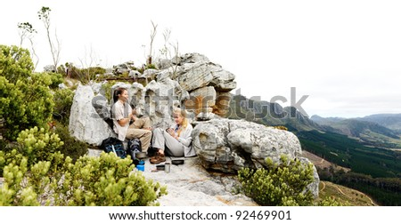 Panorama of two friends making camp after a long hike outdoors in the mountains. large file with copyspace ideal for double page spread or billboard use - stock photo