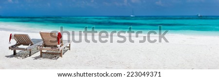 Panorama of two sun loungers with Santa hats on beautiful tropical beach with white sand and turquoise water, perfect Christmas vacation - stock photo