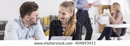 Panorama of two young colleagues,man and woman, smiling at each other while looking at a tablet - stock photo