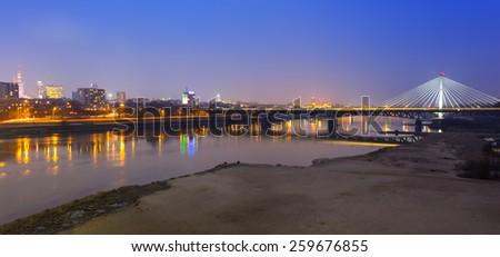 Panorama of Warsaw at night with reflection in Vistula river, Poland - stock photo