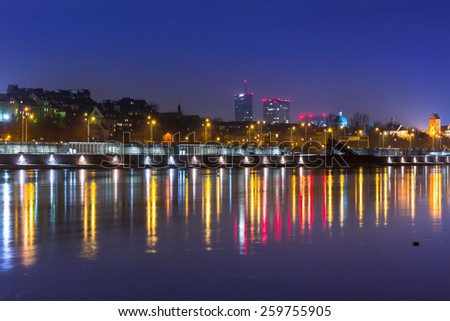 Panorama of Warsaw at night with reflection in Vistula river, Poland