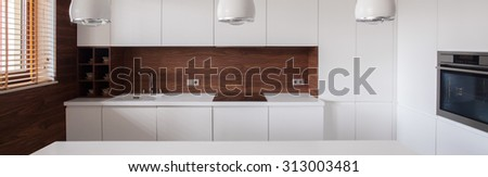 Panorama of white furnished kitchen interior with decorative lighting