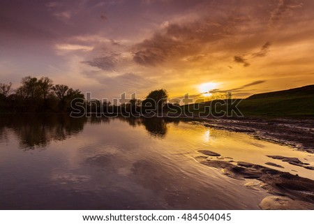 Panorama of wild river with sunset cloudy sky reflection, in autumn