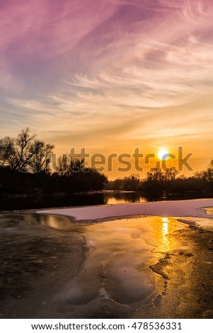 Panorama of wild river with sunset cloudy sky reflection, in winter